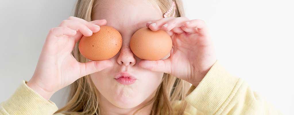 Flicka håller i ägg